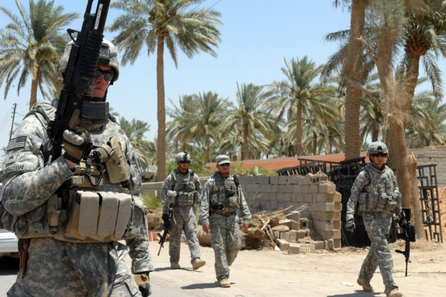 "BAGHDAD - Sgt. George Talkington (left foreground), a military police team leader from Las Cruces, N.M., Staff Sgt. Jonathan Romero (left background), a military police squad leader from San Antonio, an interpreter and Sgt. Bianca Leisure (right), an MP from Douglas, Ariz., walk back to their vehicles after checking on the progress of their Iraqi Police counterparts at a checkpoint in western Baghdad, July 24. All Soldiers are assigned to the 591st MP Company, 93rd MP Battalion, 8th MP Brigade. ""I like helping out others and being out there trying to get these people to help their country,"" said Leisure."