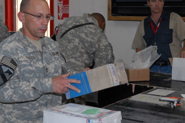 BAGHDAD - Sgt. 1st Class Eric Tizol, from San Juan, Puerto Rico, assigned to Company B, Division Special Troops Battalion, 1st Cavalry Division, prepares to mail some packages at the Camp Liberty Post Office on Victory Base Complex, July 24. Soldiers wanting to ship items home must follow the guidelines in place in order to do so. Some items, such as weapons parts and accessories, are not authorized to mail.