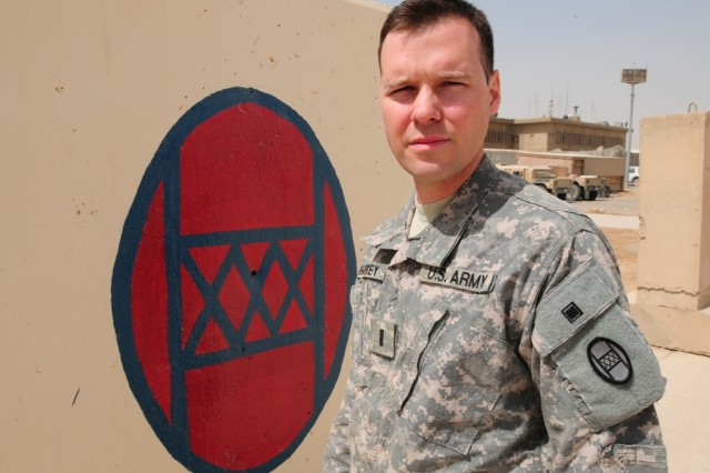 """BAGHDAD -- First Lt. Scott Sharkey of the Colorado Army National Guard's 86th Military Intelligence Company stands in front of a painted 30th Heavy Brigade Combat Team patch at Forward Operating Base Falcon July 25.   The patch, the combat version of which can be seen on Sharkey's left sleeve, dates back to the founding of the 30th Infantry Division in 1917.   Sharkey's grandfather, Allen, was attached to the division in World War II and earned a Bronze Star with """"V"""" device for valor while with the unit.   Scott wasn't aware that his grandfather had served with """"Old Hickory,"""" as the then-division and current brigade are known, until he himself learned he would be deploying to Iraq with the unit.  Sharkey hails from Centennial, Colo."""