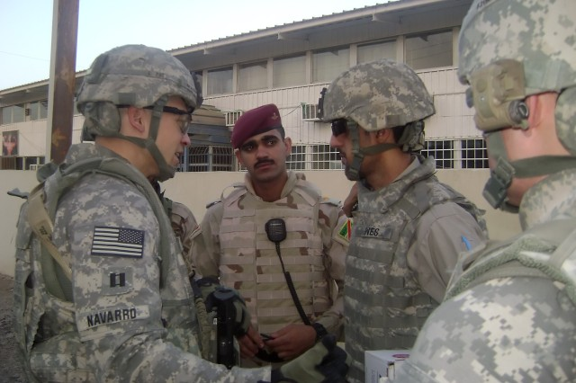 "BAGHDAD - Capt. Dustin Navarro (left), a native of Dallas, commander, Troop C, 5th Squadron, 4th Cavalry Regiment ""Longknife,"" 2nd Heavy Brigade Combat Team, 1st Infantry Division, Multi-National Division - Baghdad, speaks with a Soldier serving with the 3rd Battalion, 54th Brigade, 6th Iraqi Army Division before the Iraqi Soldiers reintegrated 24 detainees at the Adl Sports Complex July 23. The Longknife Squadron supported the IA Soldiers while the release was conducted."