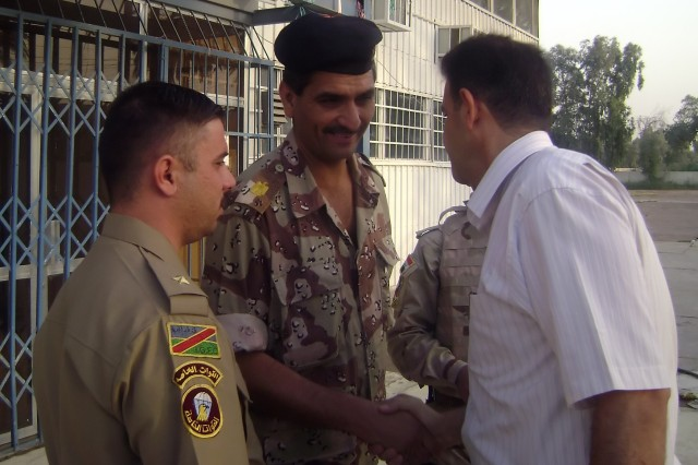 BAGHDAD - Maj. Mohammed (left), commander, Company Three, 3rd Battalion, 54th Brigade, 6th Iraqi Army Division, shakes the hand of Fouwaz, a guarantor, before the IA Soldiers reintegrated 24 detainees at the Adl Sports Facility July 23. Those chosen for reintegration were signed for by guarantors, who vouched for the character of those released.