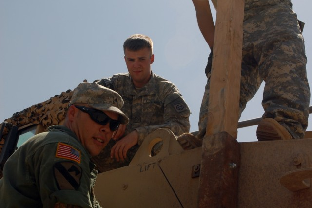 """BAGHDAD - Sgt. Corey Elliott of Dekalb, Ill., Pfc. Cory Harding of Spokane, Wash., and Pfc. John Acosta of Victoria, Texas, install a wire mitigation kit on the top of a Mine-Resistant Ambush Protected vehicle in the Division Special Troops Battalion motor pool at Camp Liberty here, July 24. The kit helps protect Soldiers from low-hanging power lines in Baghdad. Elliott and Acosta are mechanics assigned to Headquarters Support Company, DSTB, 1st Cavalry Division. Harding is an infantryman assigned the 1st Division National Police Transition Team. """"Overall, the maintenance part of the mission is critical to keeping the warfighters in the mission,"""" said Sgt. 1st Class Deighton Little, a native of Bloomfield, Conn. Little is the DSTB, 1st Cavalry Division, motor sergeant."""