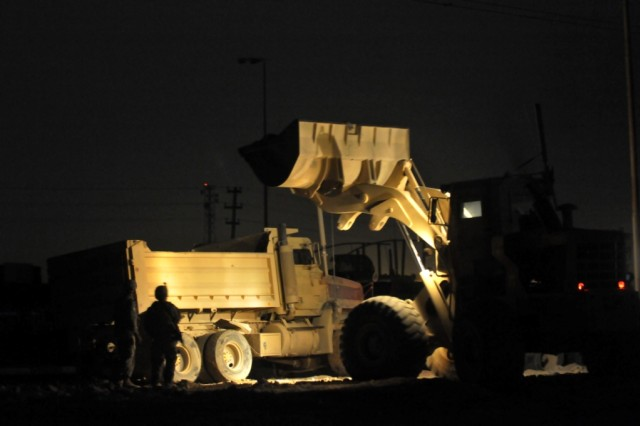 BAGHDAD - A bucket loader operator dumps concrete rubble and metal into the back of a 20-ton dump truck as Spc. Derek Fay, 46th Engineer Combat Battalion (Heavy), from Miami, Okla., oversees ground operations.  Fay provided ground guidance to ensure the loader and the dump trucks did not drive over sharp metal pieces that could puncture a tire or cause damage to the heavy engineer equipment.