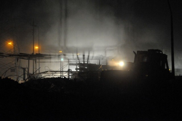 BAGHDAD - Smoke pours into the night air as bulldozer operator, Spc. Christopher Miller, Company A, 46th Engineer Combat Battalion (Heavy), 225th Engineer Brigade, of Philadelphia, knocks down the skeleton of a collapsed building in the Ghazaliyah district.