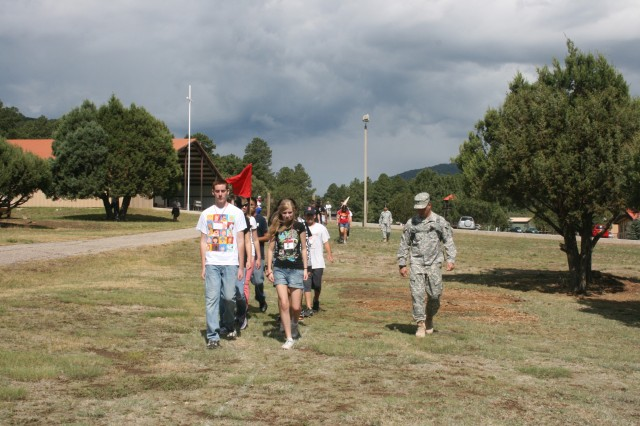 Spc. Jerry Anderson from 125th Brigade Support Battalion, 3rd Brigade, 1st Armored Division, marches youth who attended Freedom Camp at Bonita Park just outside of Ruidoso, N.M.