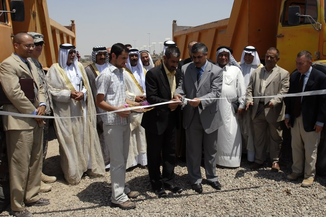 BAGHDAD - Kamil Abbas, chairman of the Abu Ghraib District Council (left center, in black suit) and Shakr Fiza, Quimaqam of Abu Ghraib, cut the ceremonial ribbon signifying the establishment of the Mobile Rural Support Team outside of the Abu Ghraib Youth Center July 26. The MRST will help the citizens of Abu Ghraib with essential services such as trash and sewage removal.