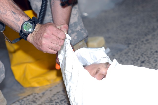 BAGHDAD - Staff Sgt Gregory Lowe uses a blade to cut away the hood of a compromised contamination suit from Sgt. Michael Kuca, demonstrating the proper way to remove a hazardous materials suit once the suit has been contaminated. Lowe is a chemical specialist from Lisbon Falls, Maine, assigned to Company A, 110th Chemical Battalion, Technical Escort Unit, and Kuca is a civil affairs specialist assigned to 425th Civil Affairs Battalion, 364th Civil Affairs Brigade, 1st Cavalry Division. The Soldiers were training Iraqi firefighters in hazardous materials handling at the Iraqi Civil Defense Directorate here, July 26.