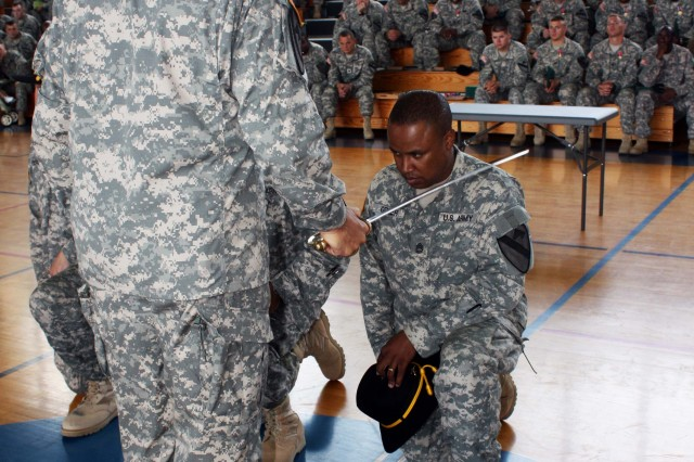 Lt. Col. Edward Bohnemann, Commander of the 2nd Battalion, 7th Cavalry Regiment, 4th Brigade Combat Team, 1st Cavalry Division performs the traditional knighting for Sgt. First Class Byron Grier during his induction into the Order of St. George at Fort Hood's Iron Horse Gymnasium July 22. Grier was one of three senior Non-Commissioned Officers at the ceremony to receive the award, which is granted to Armor and Cavalry leaders for their dedication to duty and leadership.