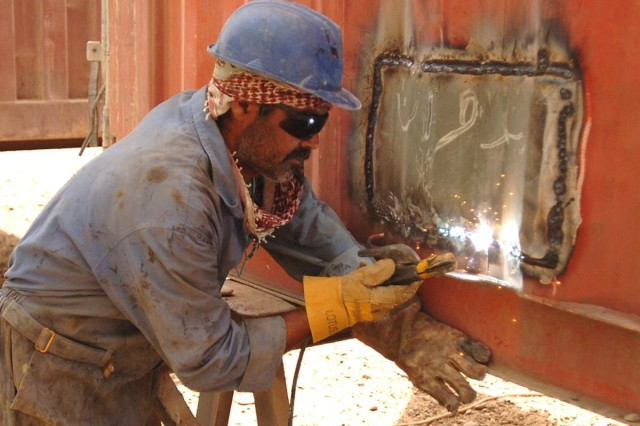 An Iraqi worker repairs a container at Joint Base Balad's Iraqi owned container repair yard.  The Miran Village Company is a project of the Iraqi Based Industrial Zone initiate that provides Iraqis with economic growth opportunities on the perimeters of installations of Coalition Forces