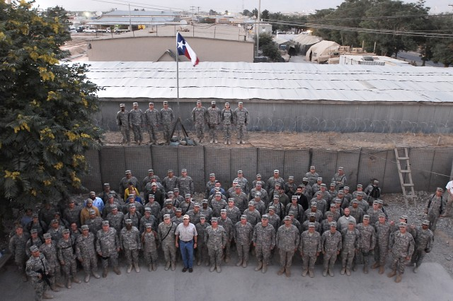 Texas Gov. Rick Perry stands with Texas service members from the 636th Military Intelligence Battalion, 71st Battlefield Surveillance Brigade and the 136th Military Police Battalion on July 20th under the Texas flag he presented to the 636th.  Both the 636th MI BN and the 136th MPs are Texas units serving in Afghanistan. The Department of Defense invited Gov. Perry and four other governors to visit service members at Bagram Air Field and Ghazni, Afghanistan. (Photo by U.S. Army Master Sgt. Ken Walker, 636th Military Intelligence Battalion Public Affairs)