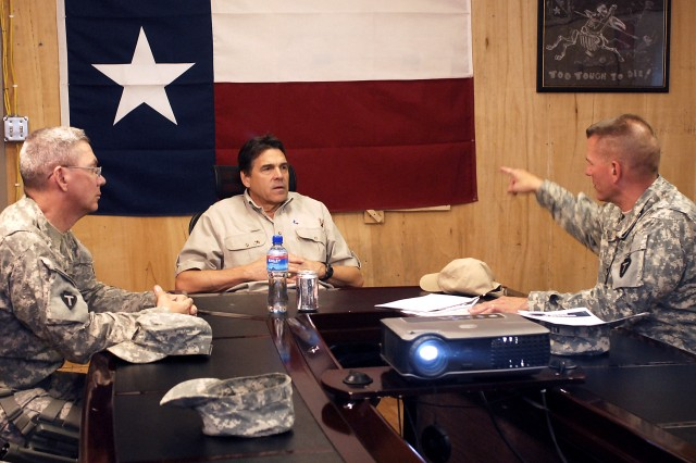 Lt. Col. Thomas J. Kleis (R) briefs Texas Gov. Rick Perry (C) as Command Sgt. Maj. Peter P.A. Collins (L) listens on the intelligence gathering successes the 636th Military Intelligence Battalion has achieved during their last six months of duty in Afghanistan. The 636th MI BN is the only military intelligence battalion currently serving in the country. Gov. Perry led a governor's delegation to Afghanistan on July 20th and 21st.  (Photo by U.S. Army Master Sgt. Ken Walker, 636th Military Intelligence Battalion Public Affairs)