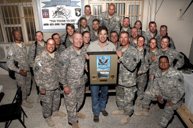 Texas Gov. Rick Perry holds a unit plaque presented to him by members of the 636th Military Intelligence Battalion stationed at Bagram Air Field, Afghanistan. Maj. Gregory H. Pollock (to Perry's right), executive officer of the 636th and Lt. Col Thomas J. Kleis (to Perry's left) commander, 636th MI BN, assist with the presentation. (Photo by U.S. Army Master Sgt. Ken Walker, 636th Military Intelligence Battalion Public Affairs)