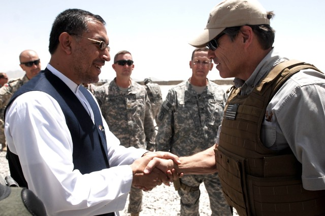 Texas Gov. Perry receives a warm greeting from Ghazni Provincial Governor Dr. Usman Usmani at the flight line minutes after landing at Forward Operating Base Ghazni by UH-60 Black Hawk helicopter. Perry led a delegation of four other governors to visit service members serving at several combat areas in Afghanistan. (Photo by U.S. Army Master Sgt. Ken Walker, 636th Military Intelligence Battalion Public Affairs)