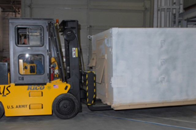 The electric forklift transports a shelter.