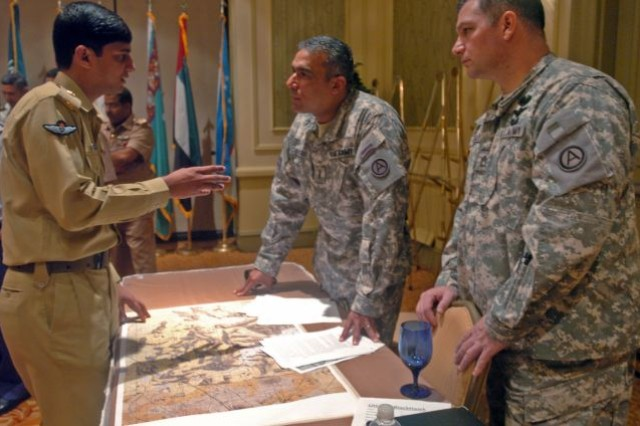 ATLANTA, Ga. (July 21, 2009) - (Pictured from left) Maj. Kamran Hashmi, Pakistan Army maintenance engineer, explains how he would approach a situation with Chief Warrant Officer Jaime Escobar, Third Army/U.S. Army Central Panther Team, and Sgt. 1st Class William O'Brien, Third Army/USARCENT Panther Team, during a scenario driven exercise at the International Aviation Symposium in Atlanta, Ga., July 21. The exercise allowed participants to work together and learn from each country's aviation programs in order to determine how to assist refugees in a mock humanitarian crisis.