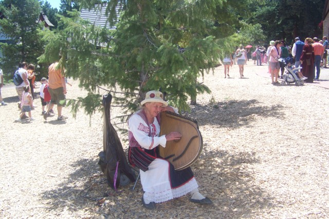 A medieval matron plays a courtly air on a harp-like instrument to welcome newcomers to Colorado's Renaissance festival, held for six weeks every summer in the village of Larkspur, Colo.