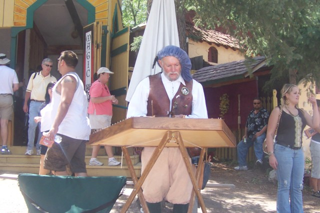 A minstrel picks out a tune on a medieval instrument to accompany faire-goers as they enjoy the smorgasboard of possibilities offered by the Colorado Renaissance Festival.