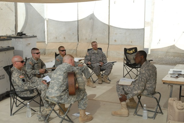 """Chaplain Glenvil Gregory (at right) of Newark, N.J., 1st battalion, 108th Field artillery chaplain, and SSG Chris Paulhamas (second from right), a chaplain's assistant, lead a general Protestant service July 25 at Fire Base Mayhem, Camp Taji, Iraq. The Soldiers of Battery B, 1-108th, 56th Stryker Brigade Combat Team taking part in the service are, from left: SPC Sean Keefer of Waynesboro, Pa.; SPC Ryan Koehler of Oil City, Pa.; SPC Jared Divittorio of Pittsburgh; and SGT Brad Hefflefinger (with guitar) of Indiana, Pa.  """""""