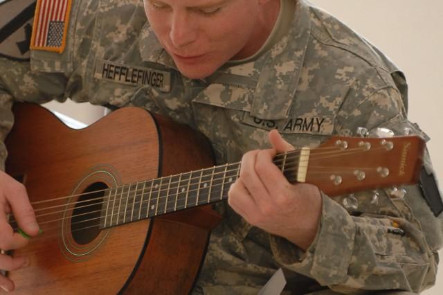 "SGT Brad Hefflefinger of Indiana, Pa., plays guitar during a worship service July 25 at Fire Base Mayhem, Camp Taji, Iraq."""