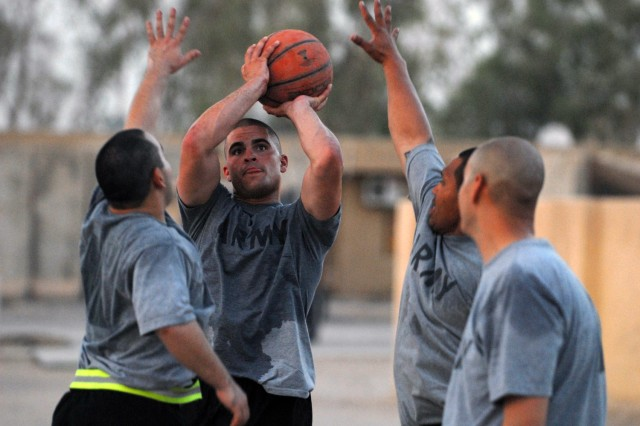 BAGHDAD - Spc. Thomas Clark (center), from Winchester, Va., assigned to 591st Military Police Company, attempts to make shot while defended by Spc. David Doxtator (left), from Keshena, Wisc., 591st MP Co. and Cpl. Paul Siko, from Pago Pago, American Samoa, assigned to Co. B, 2nd Battalion, 8th Cavalry Regiment during a pickup game at Joint Security Station Nasir Wa Salam here, July 27.