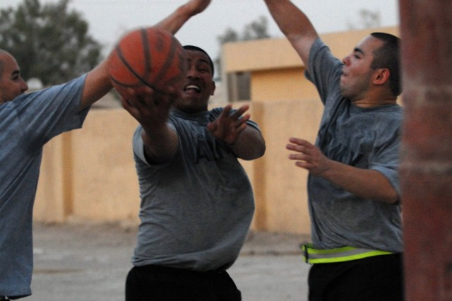 BAGHDAD - Cpl. Paul Siko (center), from Pago Pago, American Samoa, assigned to Company B, 2nd Battalion, 8th Cavalry Regiment, tries to sneak the ball past Spc. Alejandro Selaya (left) from Phoenix and Spc. David Doxtator, from Keshena, Wis., during a pickup game at Joint Security Station Nasir Wa Salam here, July 27.