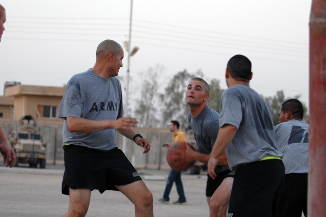 BAGHDAD - Spc. Thomas Clark (center), from Winchester, Va., assigned to 591st Military Police Company, charges toward the goal while defended by Spc. Alejandro Selaya (left) from Phoenix, assigned to 591st Military Police Co., during a friendly game of three on three, at Joint Security Station Nasir Wa Salam here, July 27.