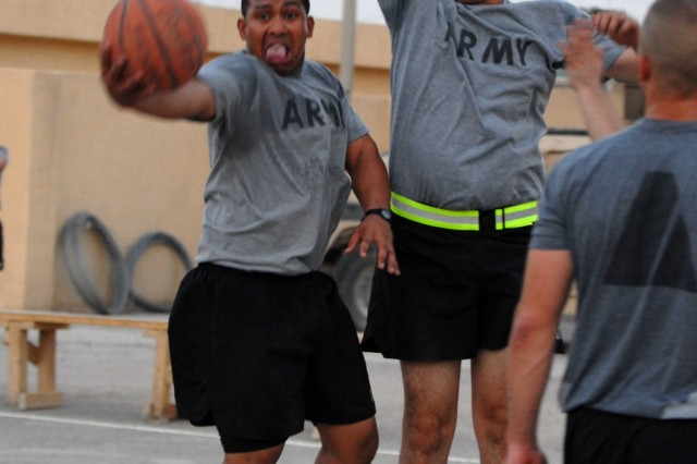BAGHDAD - Cpl. Paul Siko (left), from Pago Pago, American Samoa, assigned to Company B, 2nd Battalion, 8th Cavalry Regiment, attempts a layup while defended by  Spc. Alejandro Selaya (right) from Phoenix, assigned to 591st Military Police Co., during a game of three on three at Joint Security Station Nasir Wa Salam here, July 27.