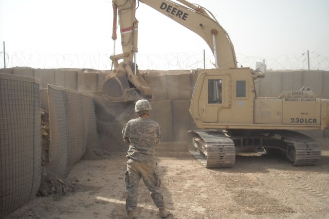 BAGHDAD - San Antonio native Sgt. Marcos Delgado, 277th Engineer Company, 46th Engineer Combat Battalion (Heavy), 225th Engineer Brigade, guides the excavator operator, Spc. Dennis Erickson, a native of Waco, Texas, during the reconstruction of a small arms weapons range at Joint Security Station Copper, July 24.