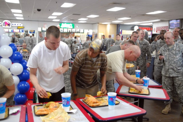 "(Third from left) Staff Sgt. Robert Hart, HHB 6-37 Field Artillery, wins the taco eating contest in Casey Post Exchange during the 114th anniversary celebration in an outstanding 5:21, saying ""I was just hungry,"" July 25."