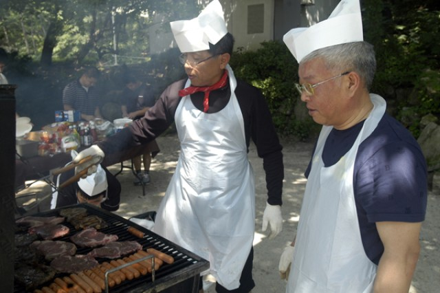 "Changhon Lee (left) and Sangkil Kim (right), 15th KSC company, cook food on a barbecue grill for 59th KSC organization day, which took place at Darakwan camp, Uijeongbu July 24. More than 150 KSC members and guests enjoyed sports, lottery and food to celebrate its 59th anniversary. ""Today is the 59th anniversary of our unit. It's a very meaningful and pleasant day,"" said Lee, Gun Tok, 15th KSC company commander. ""We gather once a year for an organization day, and I know everyone has much to say regarding our past years."" The 15th KSC Company established July 26, 1950, is a paramilitary force, which provides combat support and combat service support to the U.S. Army stationed in Area I. Although they are called ""company"" Lee said, members of KSC Company are spread among various U.S. military organizations and units to give logistics and labor support."