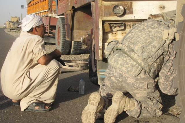 Salman Mahmoud watches as Army Mechanic Pfc. Nicholas Houston of Kinston, N.C. rigs his wrecker to Salman's trailer July 17.  Salman had a near-catastrophic blowout, and U.S. Soldiers from Special Troops Bn., 3rd Inf. Bde. Combat Team, 25th Inf. Div. who were passing by came to his rescue within minutes.