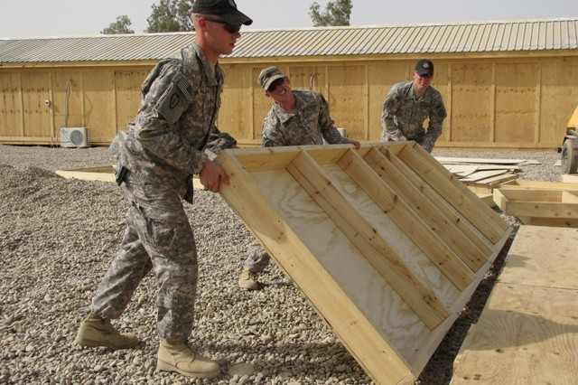 Spc. Eric Klekotka, Pfc. Jesse Harris, and Spc. Jonathan Nuss, Special Troops Battalion, 3rd Infantry Brigade Combat Team, 25th Infantry Division, build the foundation of a Military Operations and Urban Terrain (MOUT) training house that will be used by both the Iraqi Army and Coalition Forces July 15.  As part of the CF effort to rebuild the IA, joint training events will routinely take place to ensure that new Iraqi soldiers are well-equipped to handle all aspects of Iraqi security.