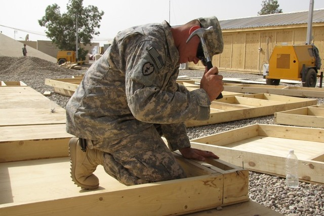 Sgt. Miles Andrews constructs a baseboard that will be used to build a Military Operations and Urban Terrain (MOUT) training house at Matar al-Saddiq July 19.  As part of the U.S. effort to help rebuild the IA's capabilities, joint training events will routinely take place to ensure that new Iraqi soldiers are well-equipped to handle the full spectrum of Iraqi security.