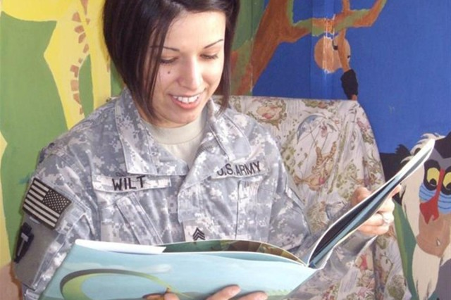 Sgt. Teresa Wilt, a native of Temple, Texas, and personnel actions noncommissioned officer, reads a book during recording for her family using the United through Reading program, a partnership between the 260th CSSB and the United Service Organization at Camp Liberty, Iraq.
