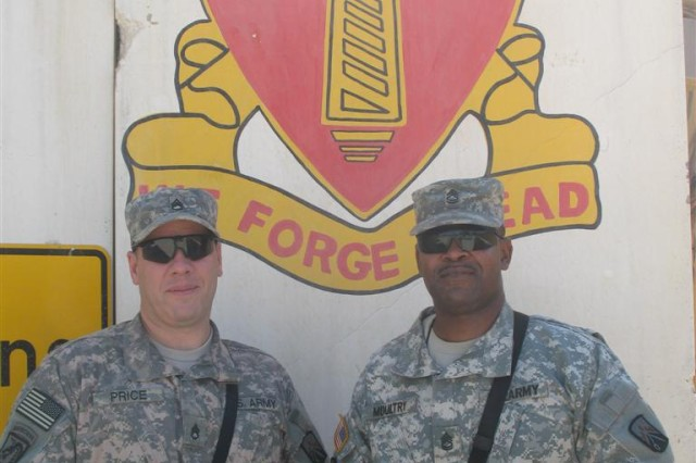 "Sgt. 1st Class Irvin Moultry, bulk and retail fuel noncommissioned officer in charge, Headquarters and Headquarters Company, 18th Combat Sustainment Support Battalion, 16th Sustainment Brigade, and Staff Sgt. Charles Price, ammunitions noncommissioned officer, HHC, 18th CSSB, pose by a battalion ""T-wall"" at Contingency Operating Site Marez-East, Iraq July 5. The Soldiers provide logistics training in support of Coalition and Iraqi units in Kirkuk, a mission designed to improve the relationship with 18th CSSB and the Logistics Training Advisory Team while advising the Iraqi Army's 4th Motorized Transportation Regiment of maintenance, refueling methods and ammunition handling procedures."