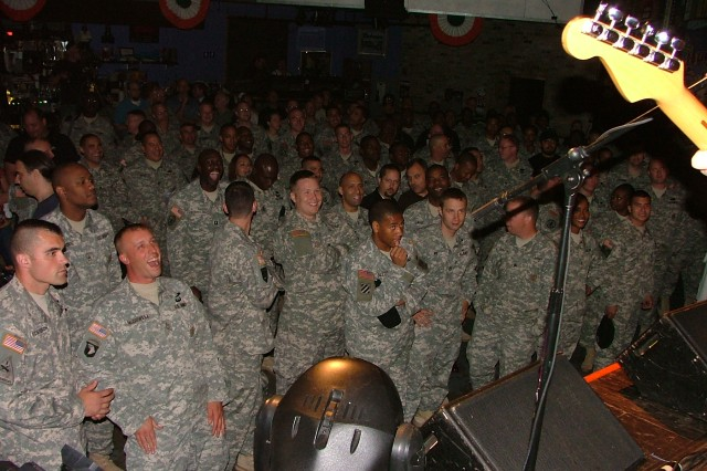 "Hundreds of IL Soldiers were part of the live studio audience for the first taping of  ""The Midnight Stage"" music show featuring different bands every week.  Soldiers here enjoy being entertained by the 101st Rock Division Band, led by Joe Cantafio.  The show was sponsored by the USO of Illinois."