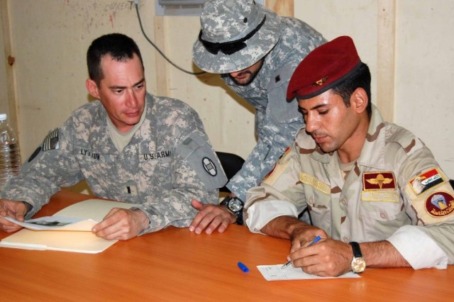 BAGHDAD - The 150th Armored Reconnaissance Squadron, 30th Heavy Brigade Combat Team, reintegrated four detainees July 28 at Forward Operating Base Falcon, who were captured about two years ago in what is now the 150th ARS area of operations. First Lt. Craig Lytton, of Charleston, W. Va.,passes information about the four to Samer Jabar Abd  of the 2nd Company, 23rd Brigade, 17th Division, through an interpreter. The Iraqi Army checked to see if the detainees had any outstanding warrants before they were released into the custody of their tribal sheiks for reintegration into their communities.