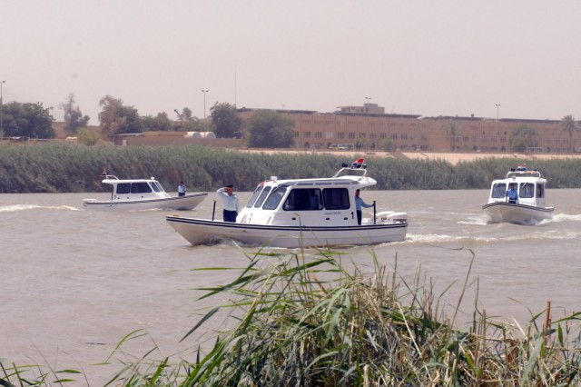 BAGHDAD - An Iraqi Police River Patrol graduates conduct a pass-in-review during their graduation ceremony on the Tigris River July 30.  The 8th Military Police, based out of Schofield Barracks, Hawaii continue to mentor and assist the Iraqi Police throughout all of their operations.