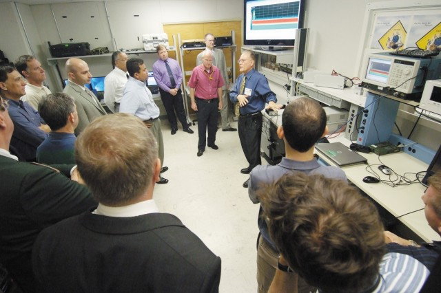 On day two of the conference, Alan Scrime, branch chief of CERDEC's Spectrum Analysis and Management Branch, joins conference attendees on their tour of a Space and Terrestrial Communications Directorate laboratory.