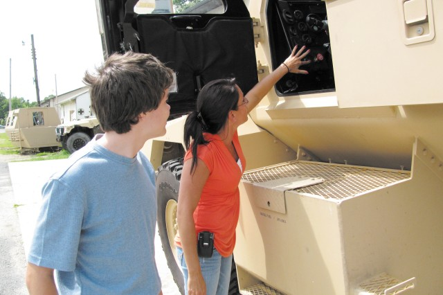 Lisa Smagala, right, an industrial engineer at the U.S. Army Edgewood Chemical Biological Center, demonstrates the Iraqi Light Armored Vehicle surrogate to Ethan Hart, a 10th-grader at Perryville High School, during a tour coordinated through the STEM Academy Summer Camp in Cecil County June 23.