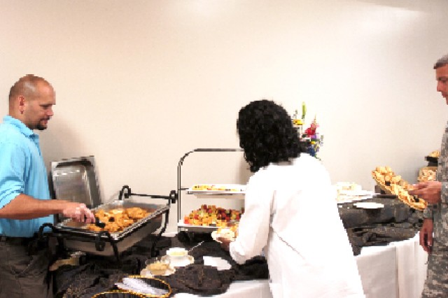 Former Army NCO Angel Ramirez, owner of Angel's catering (left),serves food at a function at Fort McPherson. Ramirez used skills learned in his 21-year Army career to start his own business.