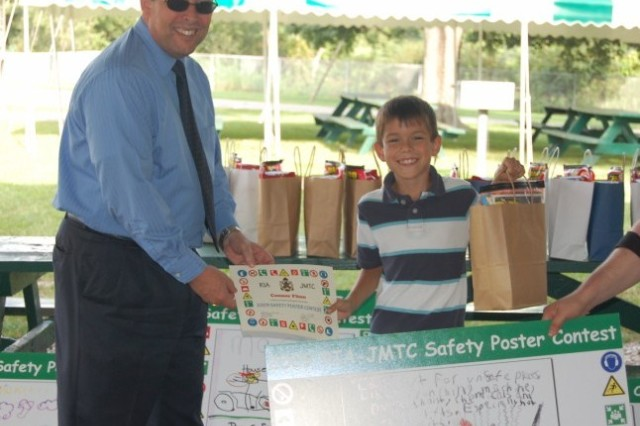 Connor Flinn holds his safety poster with RIA Deputy Command Mike Bunch.