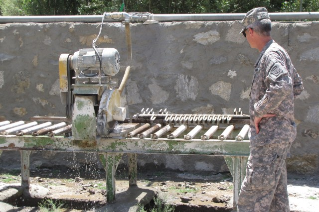 Col. Martin B. Bischoff, development chief, Combined Joint Task force-82, checks out a cutting machine used at the marble cutting and polishing plant in Panjshir, July 26. (Photo by Air Force Capt. John T. Stamm, Panjshir Provincial Reconstruction Team Public Affairs Office)