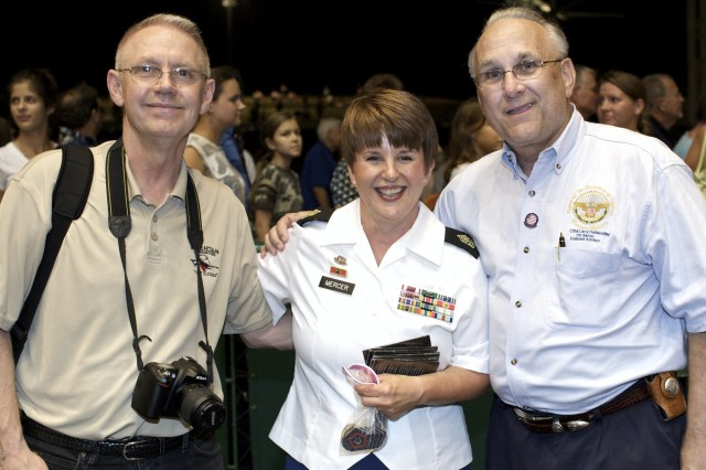 Sgt. Major Joan Mercer (center), an alto with the Soldiers' Chorus, takes time out after the show to pose for a picture with Mr. William Grimes, public affairs officer with the Houston recruiting battalion (left) and Ambassador Lawrence Holland, Army Reserve Ambassador for Texas (pictured right).