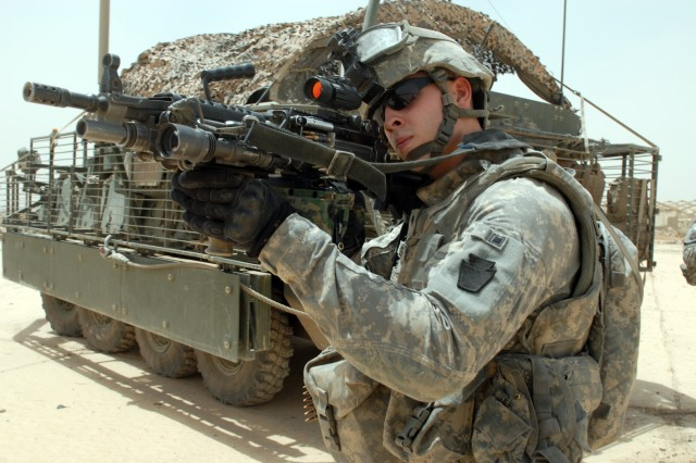 """BAGHDAD - Spc. Lucas Butler scans the horizon with the sight of his M-249 Squad Automatic Weapon during an anti-improvised explosive device and anti-indirect fire mission in the Abu Ghraib area, here, July 30. Butler is an infantryman from State College, Pa., assigned to the 2nd Battalion, 112th Infantry Regiment, 2nd Brigade Combat Team, 1st Infantry Division. The Soldiers of the 2nd Bn., 112th Inf. Regt. chose an area known as """"the big concrete slab"""" to conduct their mission to catch insurgents in the act of placing IEDs or planning IDF attacks."""