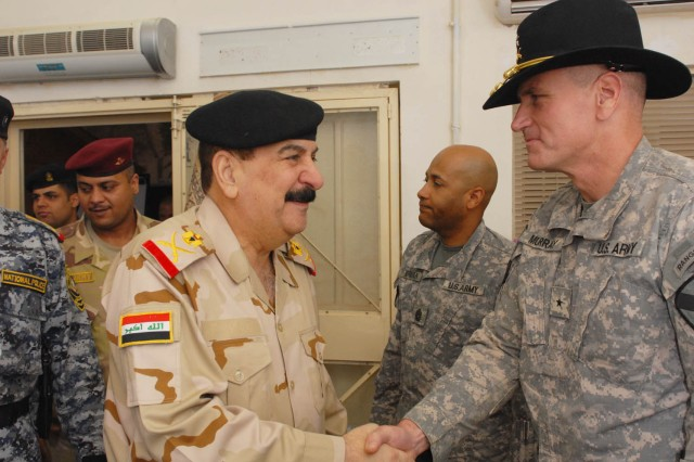 "BAGHDAD - Staff Maj. Gen. Mizher Shaher Lateef (left), 11th Iraqi Army Division commander, shakes the hand of Kenton, Ohio native Brig. Gen. John Murray (right), the deputy commanding general for maneuver for 1st Cavalry Div., Multi-National Division-Baghdad, at a farewell dinner for Mizher at Joint Security Station War Eagle, north of Baghdad, July 30. Mizher has become a good friend of the 1st ""Ironhorse"" Brigade Combat Team, 1st Cav. Div., MND-B since their arrival to Baghdad in February. At the beginning of the dinner Mizher was presented with the highest honor that the 1st Cav. Div. can offer, a stetson and set of gold spurs."