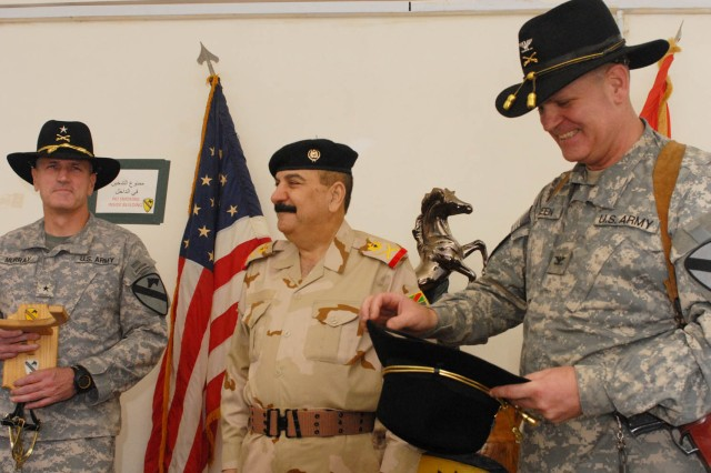 """BAGHDAD - Kenton, Ohio native, Brig. Gen. John Murray (left), deputy commanding general for maneuver, 1st Cavalry Division, Multi-National Division-Baghdad and Sioux Falls, S.D. native Col. Tobin Green (right), commander, 1st """"Ironhorse"""" Brigade Combat Team, 1st Cav. Div. present staff Maj. Gen. Mizher Shaher Lateef (center), 11th Iraqi Army Div. commander, a stetson and set of gold spurs July 30 at Joint Security Station War Eagle, north of Baghdad. Green commented that the stetson and gold spurs are a sign of close friendship between Mizher and the brigade."""