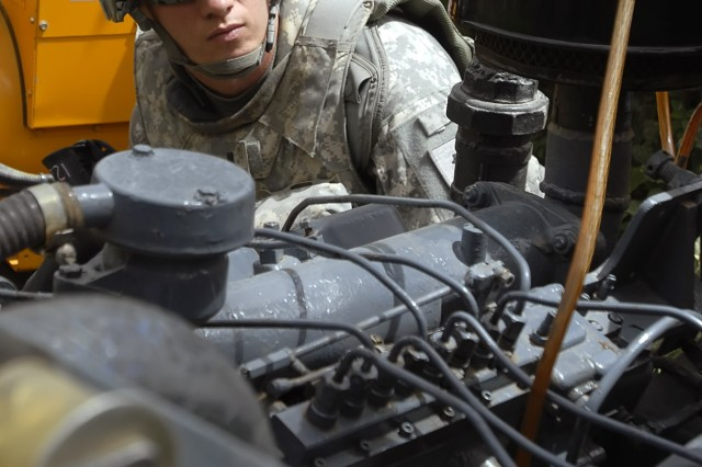 BAGHDAD - First Lt. Justin Casey, a native of Ogdensburg, N.Y., Joint Project Management Office, 2nd Heavy Brigade Combat Team, 1st Infantry Division, inspects a generator being worked on by Iraqi workers who are taking part in the Demobilization, Demilitarization and Reintegration program July 29 in the Karkh district of northwest Baghdad. Casey spent the day inspecting training sites and speaking with students and instructors about the training concerns.