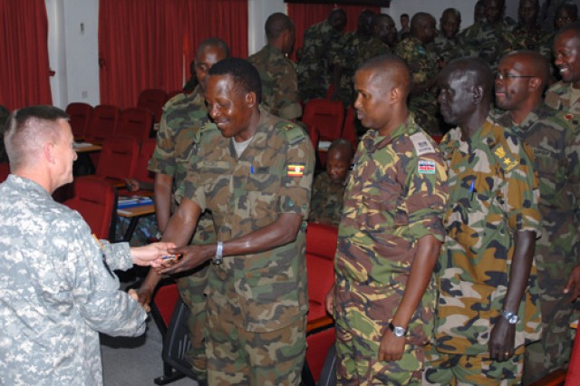 Maj. Gen. William B. Garrett III, commander of U.S. Army Africa, presents commander's coins to Kimaka Senior Command and Staff College students, during a July 30 visit to the college.