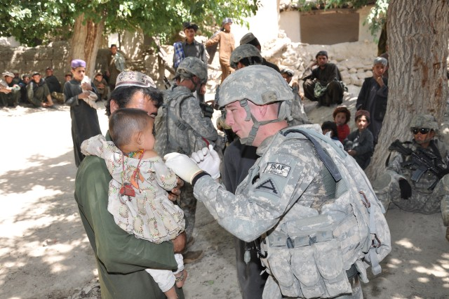 Spc. Chad E. Brown, a 1-4 Inf. Regt. combat medic from Red Oak, Texas, examines an infant girl during a dismounted patrol to a village in the Deh Chopan district of Afghanistan's Zabul province.